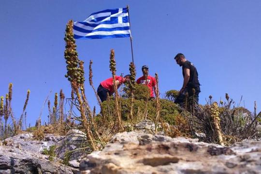 Каменос со критики до Грците кои поставија грчкото знаме на ненаселен остров
