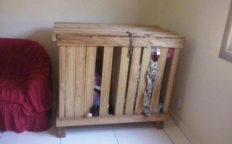 УЖАС: Ги заклучувале тригодишните близначиња во дрвен кафез додека се на работа (ФОТО)