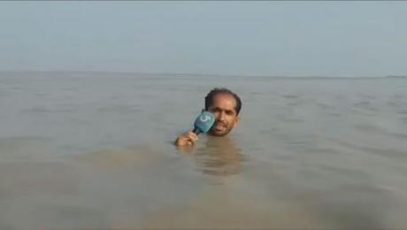 """Новинар ги """"запали"""" социјалните мрежи: Известувал за поплавите од вода, му ѕиркала само главата (ВИДЕО)"""